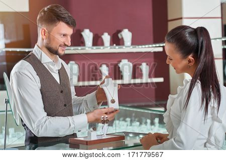 Elegance to wear. Professional jeweler smiling showing a necklace to his female customer working at his store business seller salesperson professionalism expensive present gift buying shopping concept