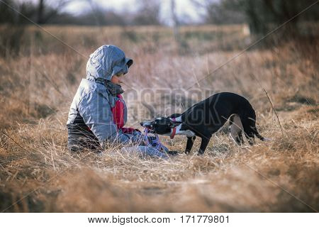 Dog bring child rope in hands for play in nature
