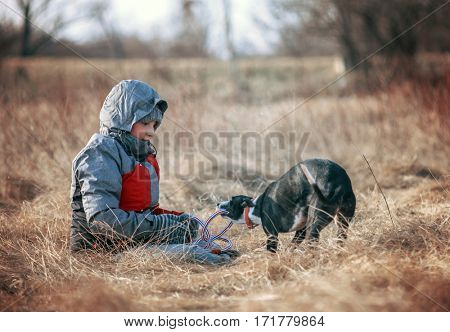 Child and dog playing outside with rope