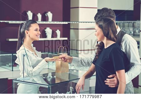 Card payments. Young happy couple buying jewelry at the store giving a credit card to a professional jeweler paying pay money modern credit card no cash consumers love couples purchase concept