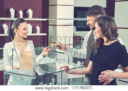 Paying for jewelry. Professional female jeweler taking credit card from her customers couple buying jewelry at the boutique bank banking payment technology love relationship consumerism toned concept