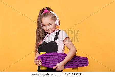 Modern teen girl holding skateboard over yellow background. Happy school girl holding brand new skateboard. New spoiled generation
