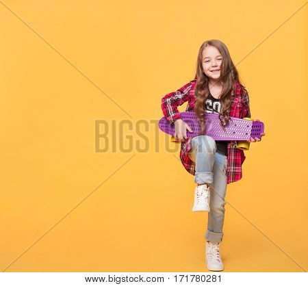 Full length little girl wearing modern casual clothing playing on skateboard like on guitar isolated on yellow background