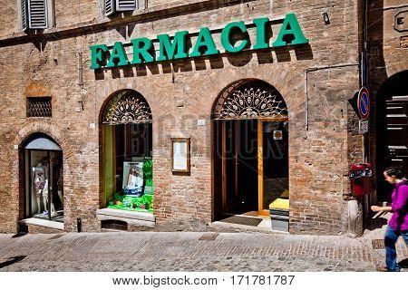 Urbino, Italy - May, 2011: Farmacia sign shop in Urbino city, Italy