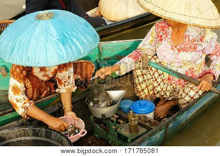 Two ladies weighing and selling fresh fish on a floating market.
