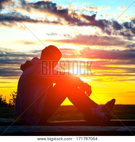 Toned Photo of Sad Teenager Silhouette at the Sunset Background