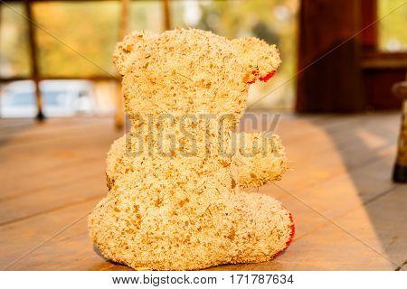 old dirty teddy bear on the wooden floor