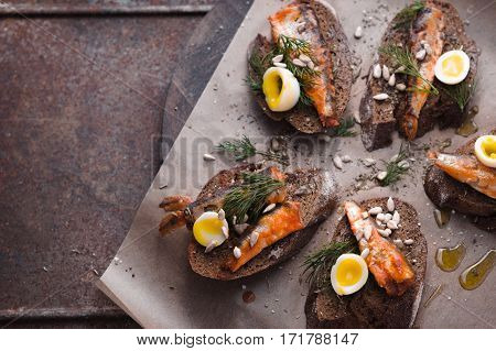 Sandwiches with sardines and quail eggs on right horizontal