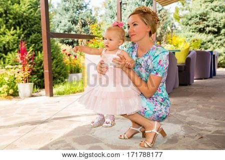 Happy mom and child girl hugging in outdoor. The concept of childhood and family. Portrait parent mother and kid. Positive human emotions feelings joy.