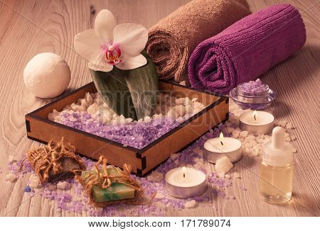 Spa setting with orchid flower box with sea salt bottle with aromatic oil soap candles and towels on wooden board