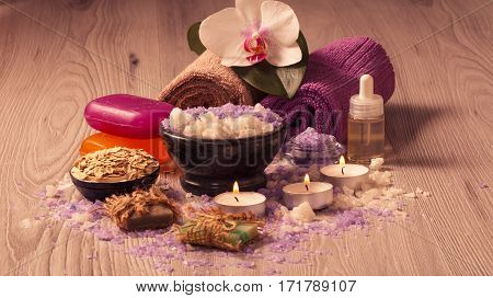 Spa setting with orchid flower bowl with sea salt bottle with aromatic oil soap scrub candles and towels on wooden board