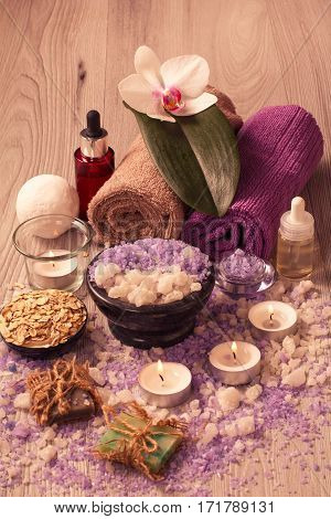 Spa setting with orchid flower bowl with sea salt bottles with aromatic oil soap scrub candles and towels on wooden board