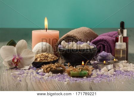 Spa composition with orchid flower bowl with sea salt bottles with aromatic oil soap scrub candles and towels on wooden board and light green background