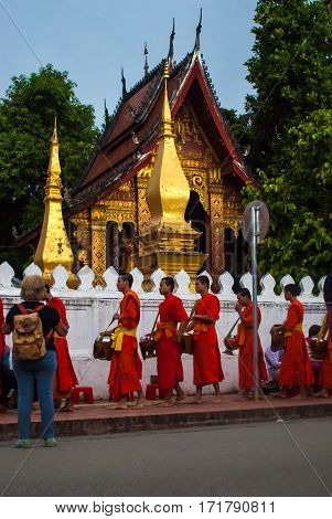 Luang Prabang, Laos - November 22, 2015: Alms giving ceremony in front of Wat Xieng Thong in the early morning, monks walking by, tourist standing close looking at them