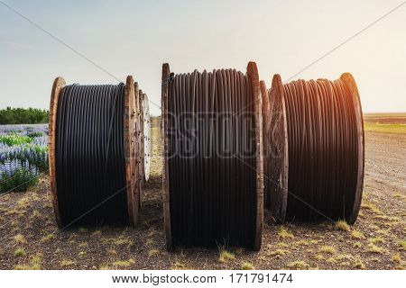 Large rolls of black wires against the blue sky at sunset