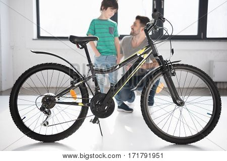 Full length view of new bicycle and happy father with son looking at each other