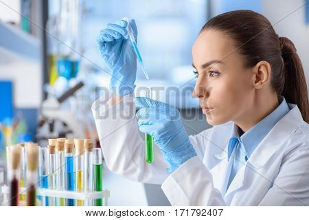 side view of concentrated scientist working with laboratory tube