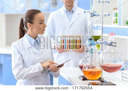Confident woman scientist holding digital tablet and inspecting reagents in lab