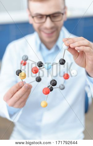Smiling man scientist in lab coat holding molecular model