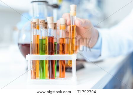Close-up view of human hand holding test tube with reagent in lab