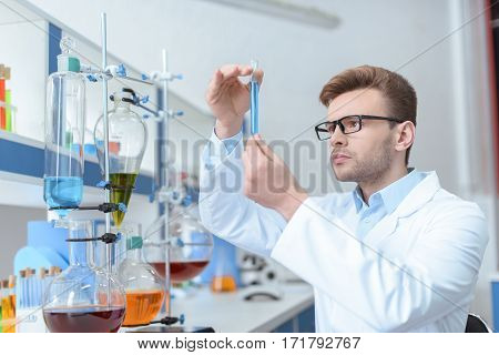Young man scientist in eyeglasses and white coat examining test tube in laboratory