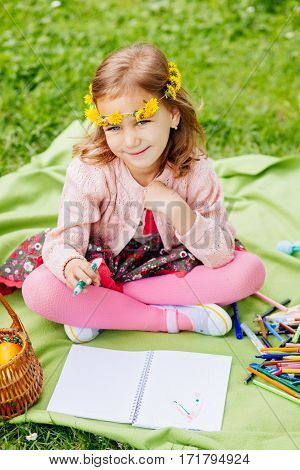 Sweet little girl drawing in the park on the blanket