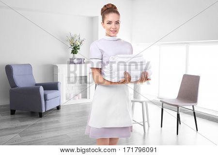 Chambermaid holding clean towels on living room background
