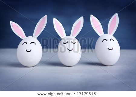 Easter eggs with paper ears on table against blue background