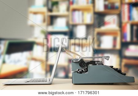 Old typewriter and laptop on table at library
