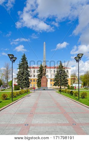 GOMEL BELARUS - APRIL 23 2016: Unidentified people walk down street near monument to Komsomol-underground fighters at intersection of Streets Karpovicha and Zharkovskogo Gomel Belarus
