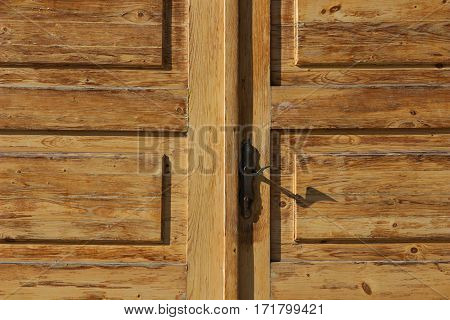 old wooden door with cracked paint and black crank