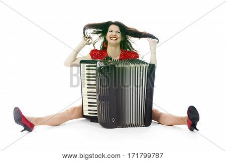 pretty woman in red has fun with accordion on floor of studio with white background