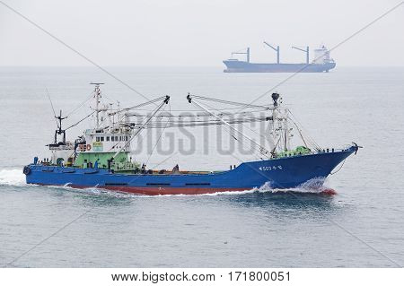 Busan South Korea - March 13th 2016: Busan anchorage of sea vessels the fishing vessel on the move and the dry-cargo ship on horizon.
