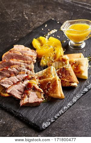 Chinese Cuisine Food - Peking Duck (Beijing Roast Duck) with Orange Sauce on Black Slate Dish. Restaurant Food on Black Slate Background