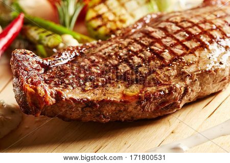 Beef Steak - BBQ Strip Steak (Grilled Beef Strip Loin Steak) with Roast Vegetables and White Sauce.