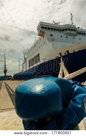 Cargo Boat's Bow and Rope Tied to Blue Bollard in Pier and Crane in background