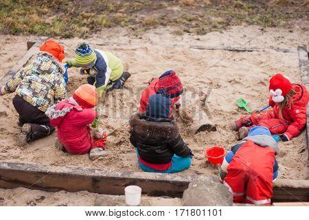 seven little kids playing in sandbox cold cloudy autumn day in Waldorf kindergarten
