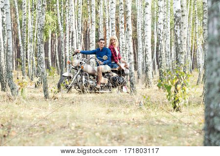 Young couple on a motorcycle in a birch grove.