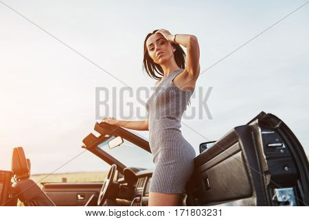Girls gladly posing next to a black car against the sky on a fantastic sunset.