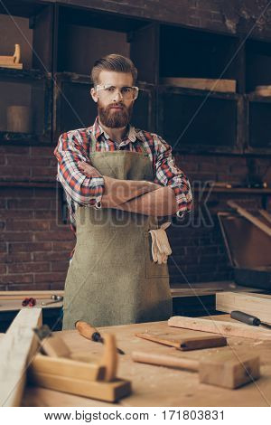 Young Handsome  Bearded Craftsman With Glasses And Hairstyle Crossed Hands Proud His Job In Workplac