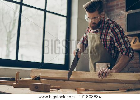 Young Stylish Cabinet-maker With  Glasses And Hairstyle. Strong  Handsome Craftsman Holding Saw And