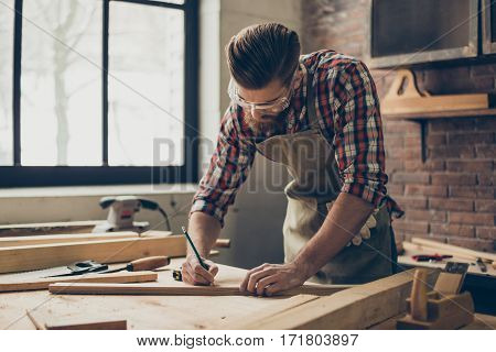 Bearded Handsome Cabinetmaker At The Tabletop With Pencil Drawing Sign On Plank.  Stylish Craftsman