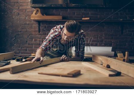 Bearded Handsome Cabinetmaker At The Tabletop With Tools.  Stylish Craftsman With Brutal Hairstyle A