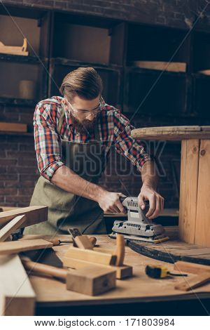 Serious Handsome  Craftsman Work With Sander For Wood. Stylish Young Cabinet-maker With Brutal Hairs