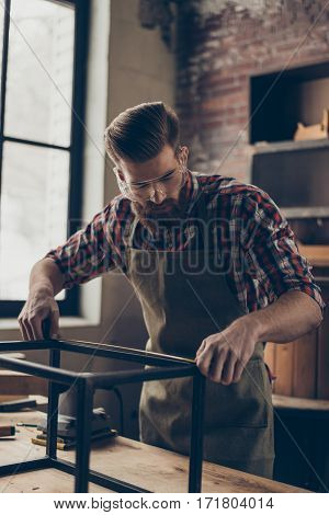 handsome craftsman work with ruler. Stylish young worker with brutal hairstyle and saved glasses work at his workplace. He love his job poster