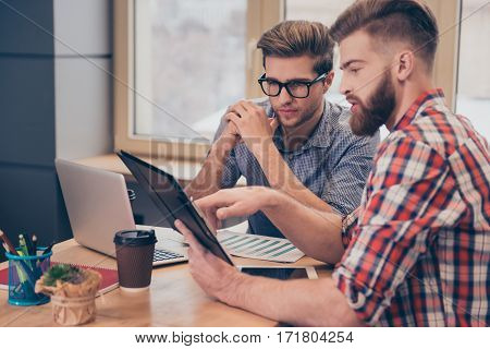 Team of two businessmen discussing new project using tablet in the office