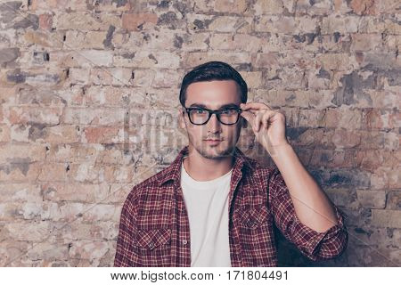 Portrait Of Confident Serious Smart Man Touching His Glasses