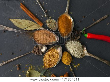 Circle Of Spoons With Different Colored Spices On Stone