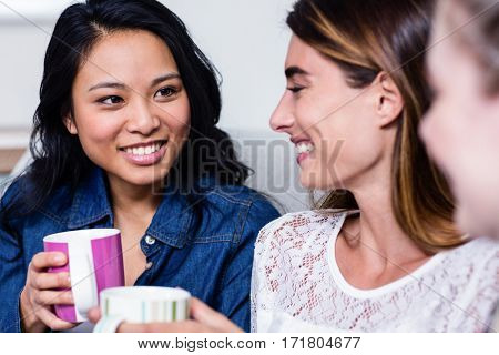 Close-up of happy female friends with coffee cup sitting on sofa at home