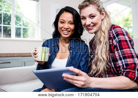Portrait of young female friends with cup and digital tablet sitting on sofa at home